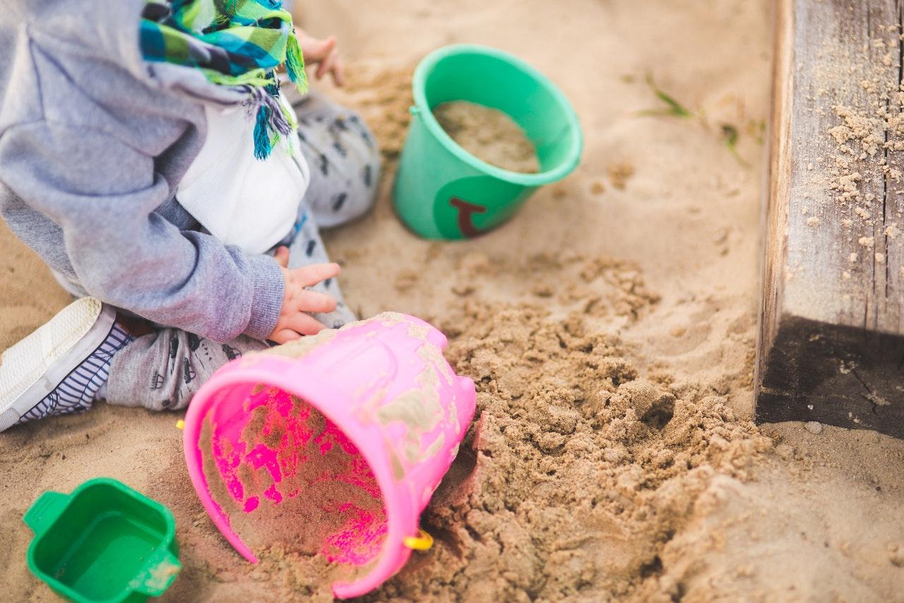 Lille dreng leger i sandkasse i have